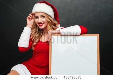 Cheerful beautiful young woman in santa claus costume with blank white board over black background