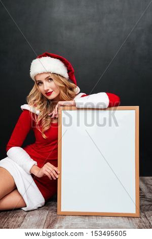 Smiling attractive young woman in santa claus costume sitting with blank white board over black background