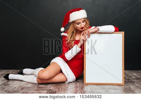 Full length of pretty young woman in santa claus costume sitting and holding white board over black background