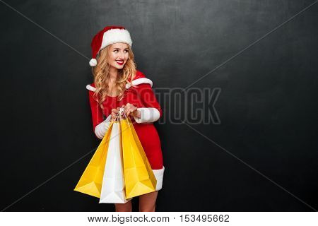 Smiling charming young woman in santa claus costume standing and holding shopping bags over black background
