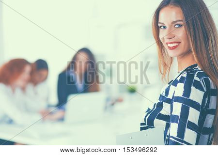 Young woman with folder writing on board in office