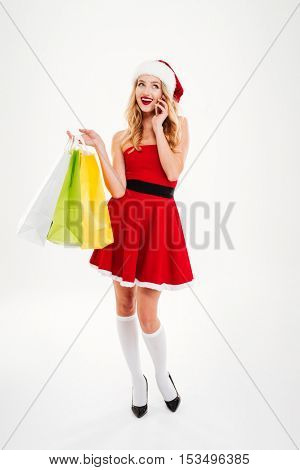 Cheerful attractive young woman in santa claus costume talking on mobile phone and holding shopping bags over white background