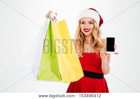 Cheerful attractive young woman in santa claus costume with shopping bags showing blank screen smartphone over white background