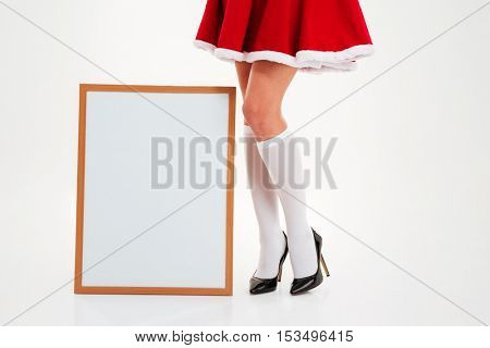 Slim legs of young woman in santa claus costume standing near blank board over white background