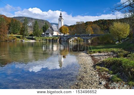 Autumn view of the stone bridge and the Church of St. John the Baptist at Lake Bohinj (Bohinjsko jezero), Slovenia