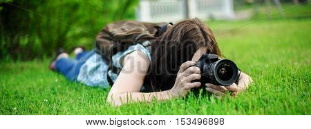 Paparazzi photographs. Photographer for the photoshoot. Girl is photographed lying in the grass exciting moments of following.
