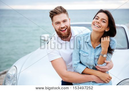 Happy smiling couple on a date standing near car at the seaside