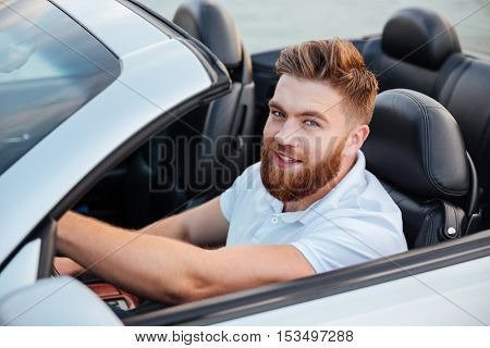 Happy young man driving cabriolet and looking at camera