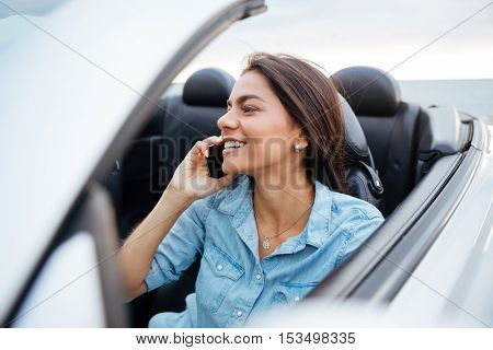 Smiling happy woman driving car and talking on mobile phone