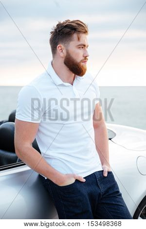 Handsome bearded man in white shirt leaning on car while standing on the beach