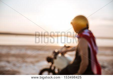 Unfocused image of man in american flag cape and helmet sitting on motorcycle