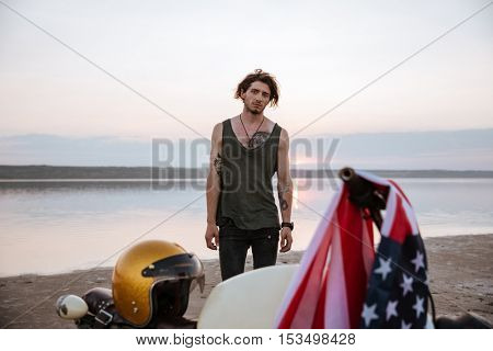 Close up of motorcycle with american flag and golden helmet with a man on the backgroud standing