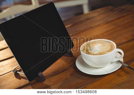 Cappuccino and digital tablet on table in cafeteria
