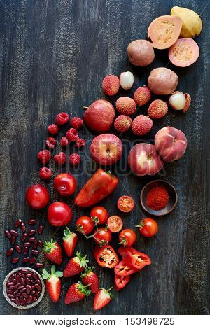 Red fruits and vegetables laid across a dark distressed background in a gradient scale artistic food background