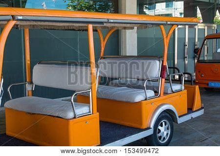 Back side of tour bus. Opened orange electrical car without any people