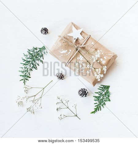 Christmas composition. Christmas gift, pine cones, thuja branches and gypsophila flowers. Top view, flat lay, square