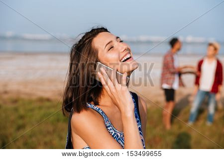 Cheerful attractive young woman talking on cell phone and laughing outdoors