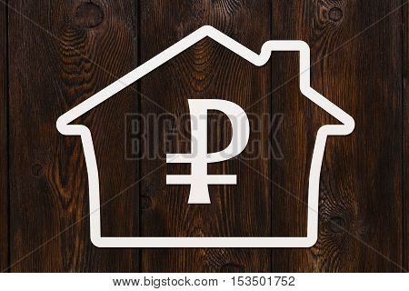 Paper house with ruble sign inside. Housing, money concept. Dark wooden background. Abstract conceptual image