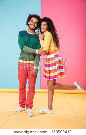 Portrait of smiling african young couple in clothes standing together over colorful background