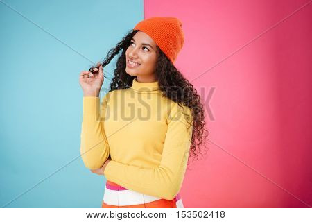 Smiling thoughtful african young woman in hat standing and thinking