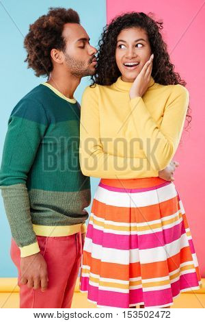 Happy tender young couple smiling and kissing over colorful background