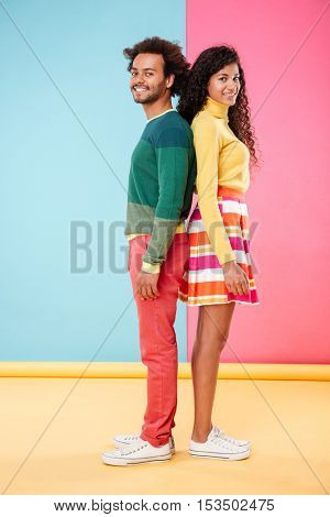 Full length of happy african young couple standing back to back and smiling over colorful background
