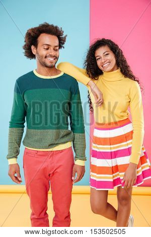 Happy relaxed african young couple standing together over colorful background