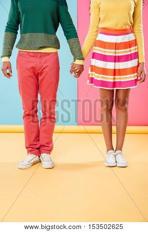 Legs of young couple standing and holding hands over colorful background
