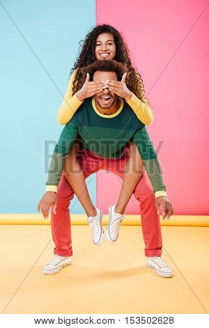 Cute amusing african american young man holding his girlfriend on his back
