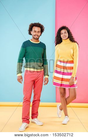Beautiful african american young couple in bright clothes standing and winking over colorful background