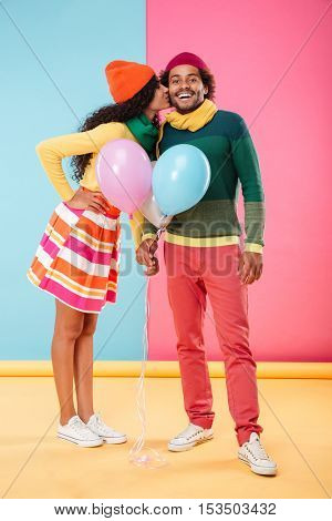 Full length of smiling african young couple in hats and scarves holding balloons and kissing