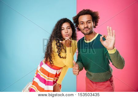 Happy african young couple sending kiss and showing ok sign over colorful background