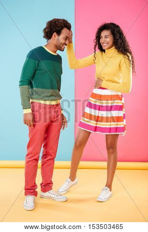 Full length of happy african young couple standing and laughing over colorful background