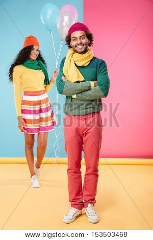 Happy african young woman with balloons walking on date to her boyfriend