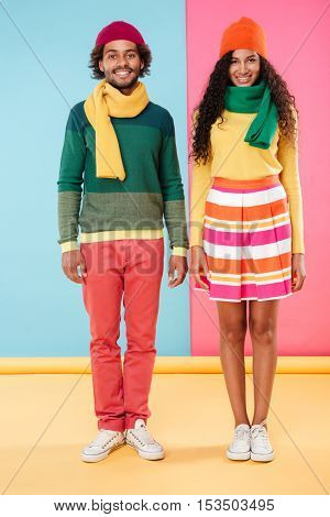 Full length of cheerful african american young couple in scarves and hats standing