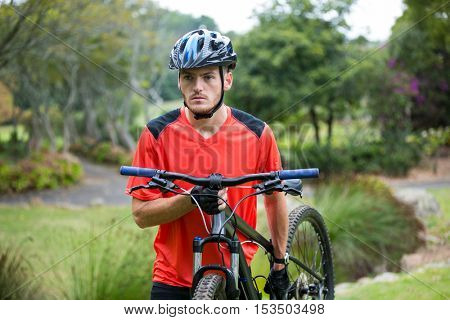 Male cyclist carrying mountain bike while walking in park