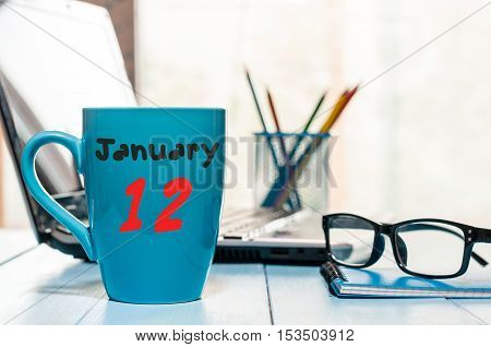 January 12th. Day 12 of month, Calendar on cup morning coffee or tea, Database Administrator workplace background. Winter time. Empty space for text.