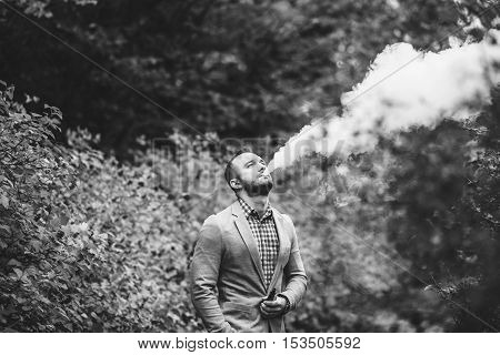 Men With Beard Smoking Electronic Cigarette Outdoor