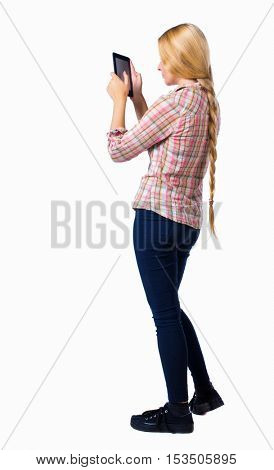 back view of standing young beautiful  girl with tablet computer in the hands of. girl  watching. .  Isolated over white background. blonde in a black pants work on the tablet.