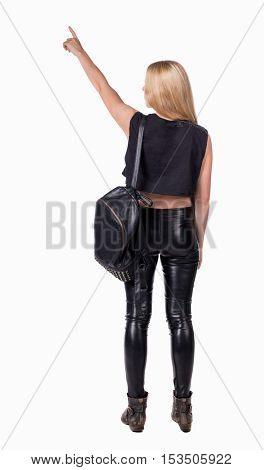 Back view of  pointing woman with backpack. beautiful girl. Rear view people collection.  Isolated over white background. Blonde in leather pants standing with backpack standing and shows his hand up