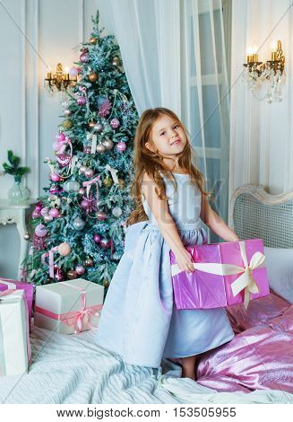 happy girl with Christmas tree and presents in her room at home