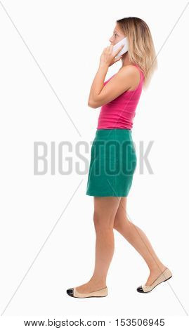 side view of a woman walking with a mobile phone. back view ofgirl in motion.  backside view of person. Isolated over white background. Girl in a green skirt misses talking on the phone.