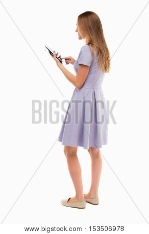 back view of standing young beautiful  girl with tablet computer in the hands of. girl  watching. Isolated over white background.Skinny girl in a blue dress and working on the tablet.