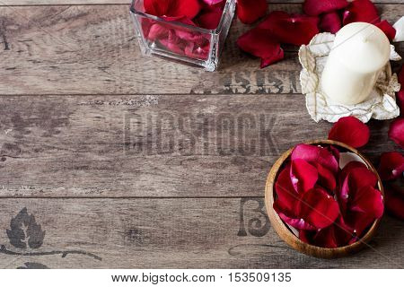Glass Vase And Wood Bow Filled With Red And White Rose Petals, White Aromatic Vanilla Candle. Wooden