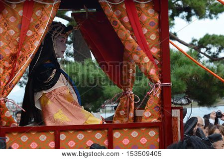 KYOTO, JAPAN - OCTOBER 16, 2016 - Japanese shrine maiden looks out from her carriage in the Saigu Procession festival in Kyoto