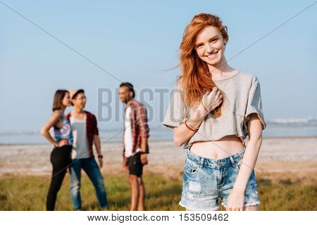 Happy redhead young woman standing while her friends talking outdoors