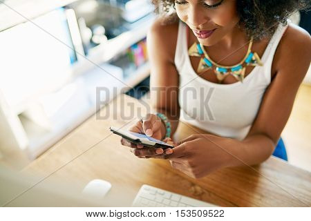 Stylish young businesswoman checking her mobile phone for text messages as she sits at her desk in an office close up high angle cropped view