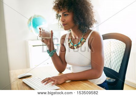 Young attractive African American businesswoman drinking water as she sits at her desk typing information on a desktop computer