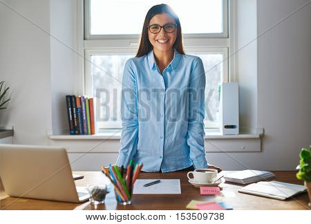 Happy successful young female entrepreneur with a confident smile standing leaning on her desk in her home office smiling at the camera