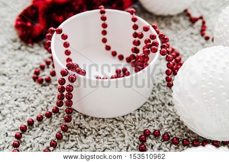 Preparing for the New Year holidays. Red beads for decoration a Christmas tree in a white box